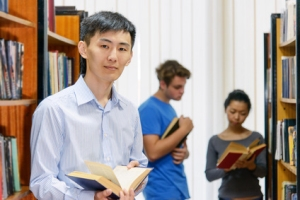 Student standing by bookshelf in library